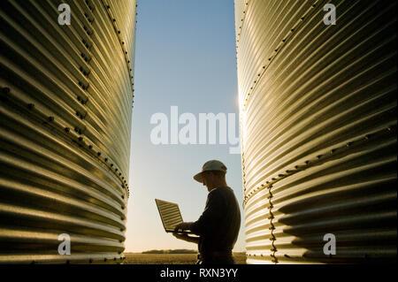 a farmer using a computer next to his on farm grain storage bins, near Dugald, Manitoba - Stock Image