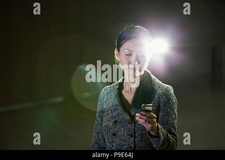 An Asian businesswoman in a spotlight working with her cell phone. - Stock Image