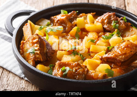 Homemade stew of short beef ribs with potatoes in a spicy sauce closeup in a pot on the table. horizontal - Stock Image
