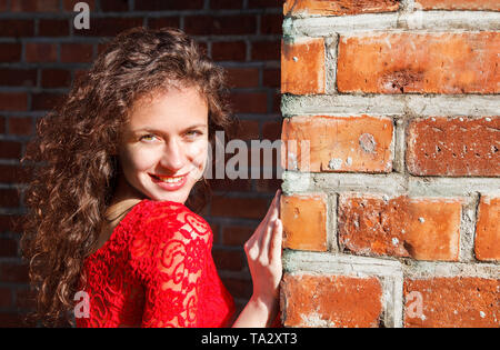 portrait of a young smiling beautiful spanish girl in red dress near the brick wall outdoor on sunny summer day - Stock Image