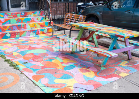 Colourfully painted entrance of walkway, stairs and picnic table in front of a bar in Kensington Market in downtown - Stock Image