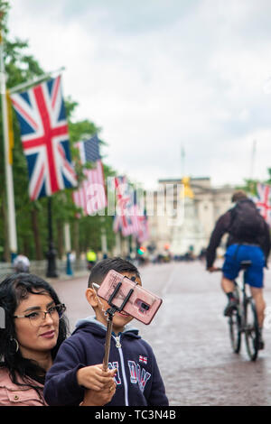 A woman takes a selfie with her son with the view of Union and American flags on The Mall with Buckingham Palace in the distance - Stock Image