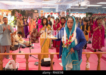 A devout Hindu woman celebrates her 70th birthday by assisting in the service and performing the ritual of aarti, spreads fire in front of the deities - Stock Image