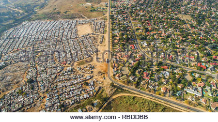 Kya Sands / Bloubosrand. AMAZING aerial images have captured the stark contrast and inequality where rich meets poor all across the world. The spectacular bird's eye view pictures show the landscape as an affluent area gives way onto one where people may be suffering from poverty. The stunning shots show this crossover of the rich and poor all across South Africa, Kenya, Mexico and even the USA. The remarkable photographs form of africanDRONE founder and photographer Johnny Miller's (37) Unequal Scenes project. Johnny Miller / mediadrumimages.com - Stock Image