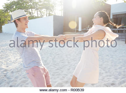 Young couple holding hands while spinning on beach - Stock Image