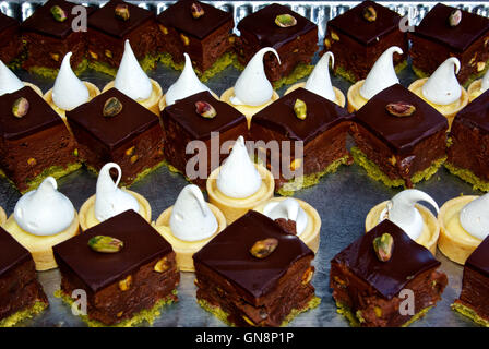 Chocolate pistachio brownies with icing & lemon custard pastry tarts whipped cream - Stock Image