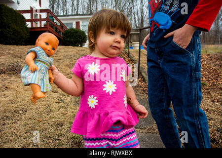 A 15-month old toddler girl walks while holding a doll outside on a summer day. - Stock Image