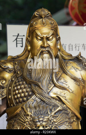 Closeup of a bronze sculpture of the ancient Chinese warrior-god Guan Yu displayed on a street of Pokhara, Nepal. - Stock Image