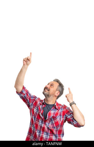 Joyful man pointing with index fingers and looking at blank copyspace above head isolated on white background - Stock Image