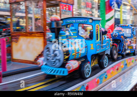 A young boy enjoys a ride with Thomas the Tank Engine in a fun fair in a city centre. - Stock Image