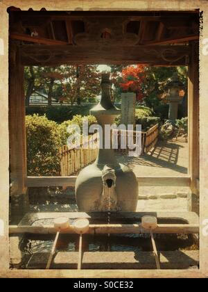 Chozuba or outdoor well for ritual cleansing of hands and mouth when visiting shrines or temples, with hishaku or - Stock Image