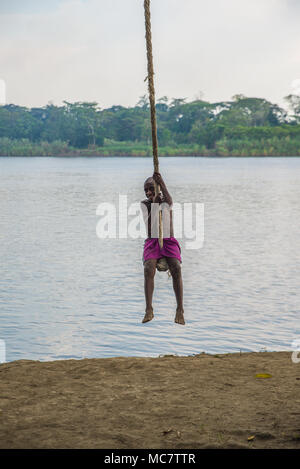 A boy swinging on a rope over Sepik River, Korogo Village, Middle Sepik, Papua New Guinea - Stock Image