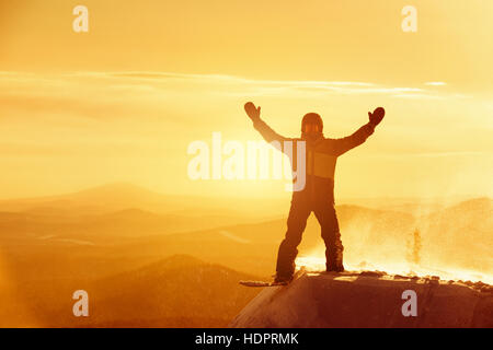 Happy snowboarder win winner pose ski resort sunset - Stock Image