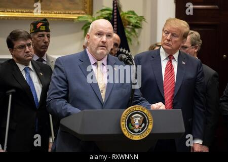 U.S President Donald Trump, right, listens as Thomas Winkel of the Arizona Coalition for Military Families speaks during a signing ceremony for an executive order calling for the Prevents Initiative in the Roosevelt Room of the White House March 5, 2019 in Washington, DC. The initiative calls for a National Roadmap to Empower Veterans and End a National Tragedy of Suicide. - Stock Image