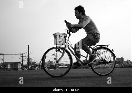 Cycling and messaging in Tokyo - Stock Image