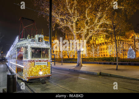 Budapest, Hungary - Festively decorated light tram (Fenyvillamos) on the move with Parliament of Hungary at Kossuth square by night. Christmas season  - Stock Image