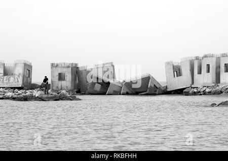Italy. Concrete blocks on sea water - Stock Image