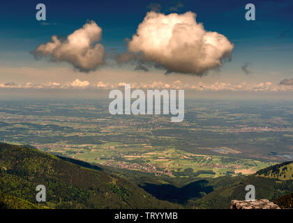 View from Mount Wendelstein in Upper Bavaria in the late Spring, featuring the valley below, towns and partly cloudy blue sky - Stock Image