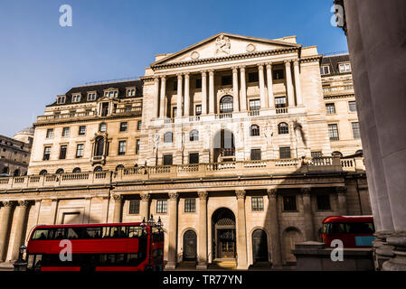 Red London buses outside the Bank of England, London, UK - Stock Image