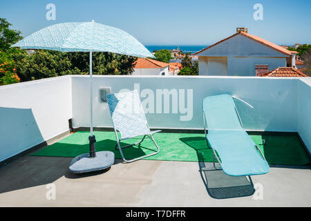 Sun beds and umbrellas on terrace in a luxury summer resort with Atlantic sea view in Cascais, Portugal. - Stock Image