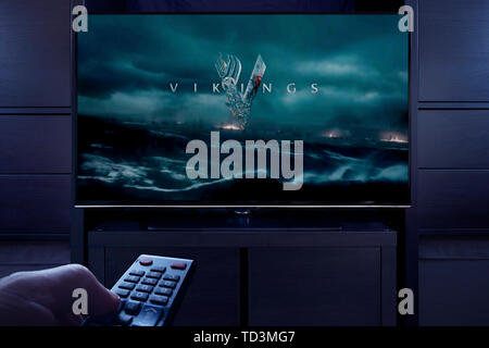 A man points a TV remote at the television which displays the Vikings main title screen (Editorial use only). - Stock Image