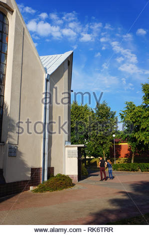 Poznan, Poland - July 10, 2018: Woman and man standing in front of a church entrance on the Stare Zegrze district - Stock Image
