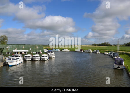 Boats moored at Ludham Bridge Boatyard on the River Ant on the Norfolk Broads. - Stock Image