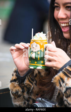 Pretty girl enjoying a Punsch topped with whipped cream in ceramic mug at Christmas Market at Belvedere Palace, Vienna, Austria. - Stock Image
