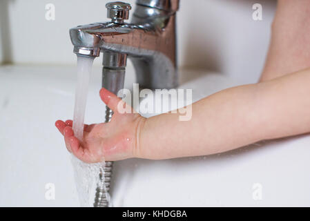 Child's hand testing bath water temperature - Stock Image