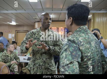 SAN FERNANDO CITY, Philippines (July 14, 2018) Capt. Lex Walker, Commodore, Destroyer Squadron 7, discusses engagement activities with Philippine Navy Commodore Nichols Driz, Commander, Naval Forces Northern Luzon, at the closing ceremony of Maritime Training Activity (MTA) Sama Sama 2018 aboard Philippine Navy ship BRP Tarlac (LD-601). The week-long engagement focuses on the full spectrum of naval capabilities and is designed to strengthen the close partnership between both navies while cooperatively ensuring maritime security, stability and prosperity. - Stock Image