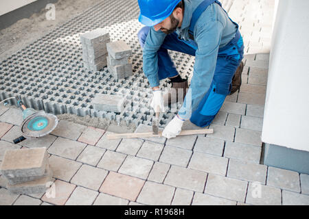 Builder laying paving tiles on the construction site, cropped image with no face - Stock Image
