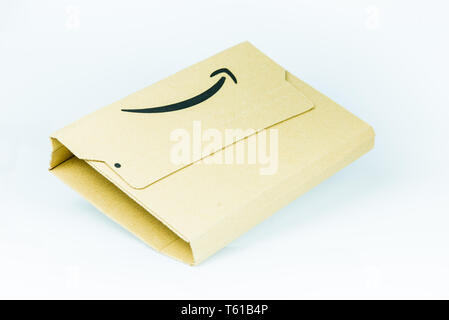 A parcel with Amazon logo on white background. - Stock Image