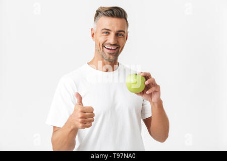 Portrait of healthy man 30s having bristle in casual t-shirt posing on camera and holding green apple in hand isolated over white background - Stock Image
