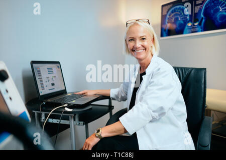 Portrait Female Doctor Working In Hospital Office With Computer Smiling - Stock Image