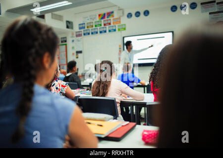 Junior high school students watching teacher give lesson at projection screen in classroom - Stock Image