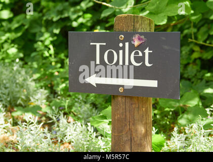 A slate sign giving directions to the toilet. - Stock Image