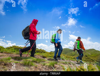 Family with backpacks hiking on summer vacation in mountains - Stock Image