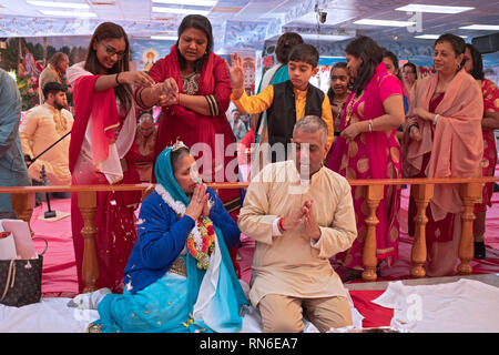 A Hindu woman celebrates her 70th birthday assisting in the service and, as is the custom, gets flower petals sprinkled on her as a blessing. in NYC. - Stock Image