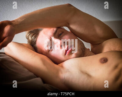 Shirtless sexy male model lying alone on his bed in his bedroom, looking at camera with a seductive attitude - Stock Image