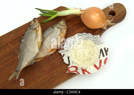 Dried fish, onions and salt on a board on a white background - Stock Image
