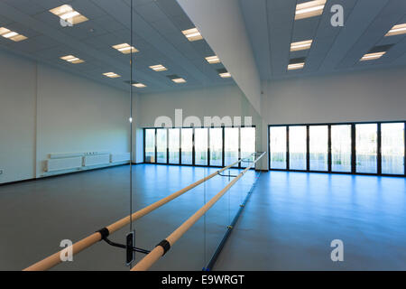 Unoccupied dance studio with mirrors and ballet barre - Stock Image