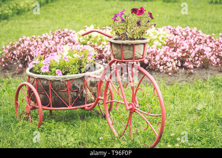 Flowerbed in the shape of a retro bicycle with baskets and flowers - Stock Image