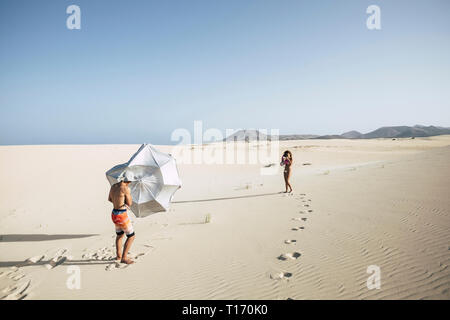 Scenic image with man playing with the wind and umbrella sun on the big beach or desert dunes and woman taking pictures to him - vacation and travel c - Stock Image