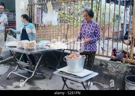 Older Vietnamese woman street vendor making banana crackers over an open flame in a bucket - Stock Image