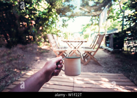 view of a hand of a hiker person resting with a cup in a camping, travel discovery concept, point of view shot - Stock Image