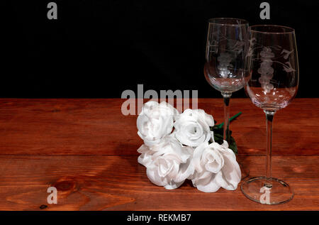 Beautiful etched wine glasses with awhite roses on wooden table and dark background. Valentines, Mothers Day, Easter, Christmas, Wedding Concepts - Stock Image