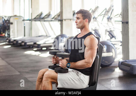 Side view portrait of young adult man muscular built handsome athlete working out in a gym, sitting on bench and holding two dumbbell on the knees. in - Stock Image
