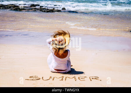 Travel people and summer at the beach concept - outdoor holiday vacation leisure activity - woman with hat and white dress viewed from rear sit down o - Stock Image