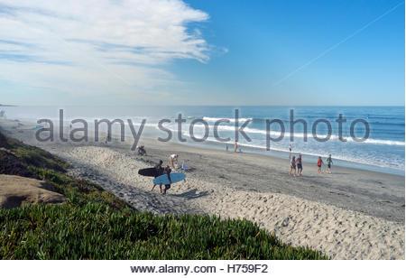 Surfers walk towards the sea, in Del Mar (San Diego County) in California, USA. - Stock Image