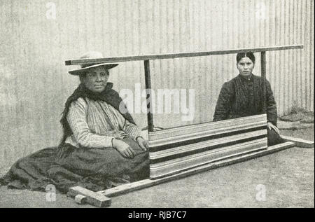 Two Araucanian women weaving guanaco wool, southern Chile, South America. Araucania (Araucana) is an indigenous area of Chile inhabited by the Moluche (Mapuche) people. - Stock Image